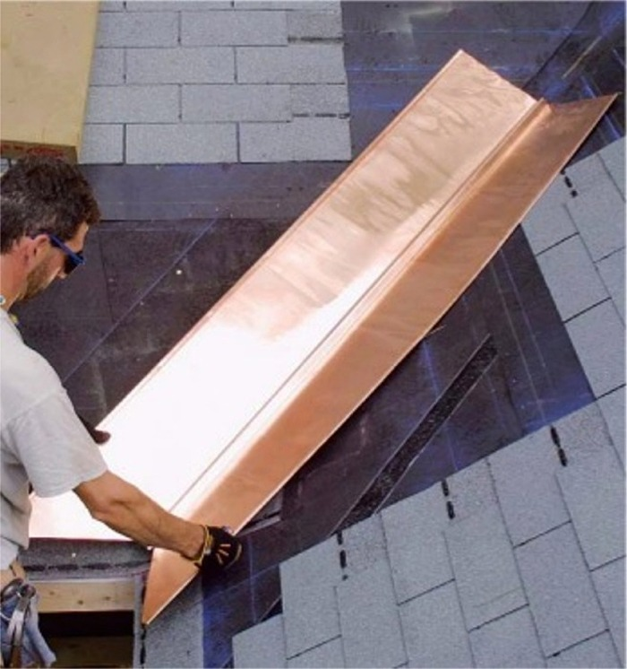 A 'W'-shaped copper sheet is placed in the center of a roof valley.