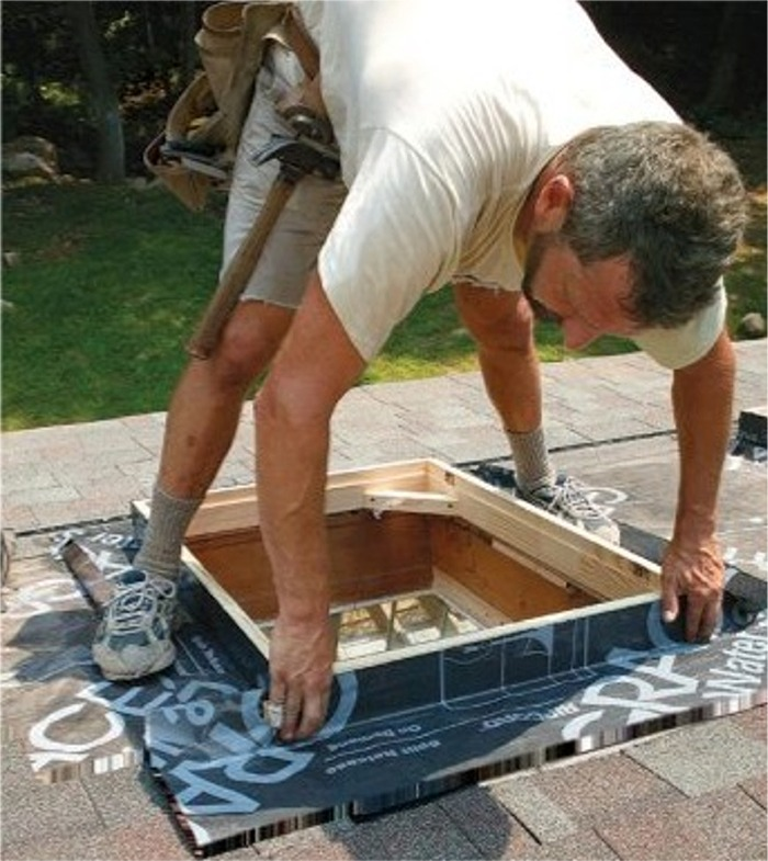 Skylight curb on a roof being wrapped with self-adhering membrane as backup protection to the primary roof flashing.