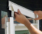 A tab cut in the top piece of window trim wraps over the side to divert water