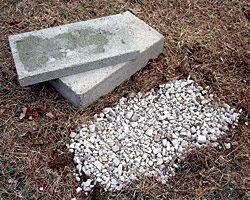 shallow bed of gravel placed underneath concrete foundation blocks aids drainage and helps prevent them from sinking into the soil.